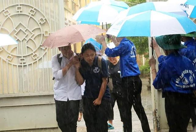 Thí sinh Hà Nội ra về trong mưa. (Ảnh: Mai Châm)
