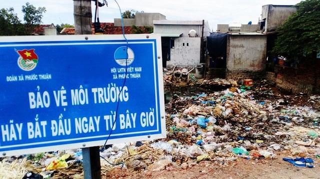Sau tấm biển bảo vệ môi trường là bãi rác bao vây nhà dân.