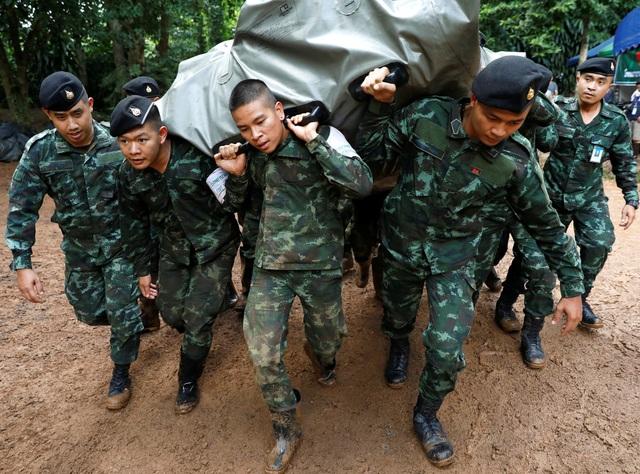 Các binh sĩ khiêng hàng cứu trợ được chuyển tới khu vực tìm kiếm. (Ảnh: Reuters)