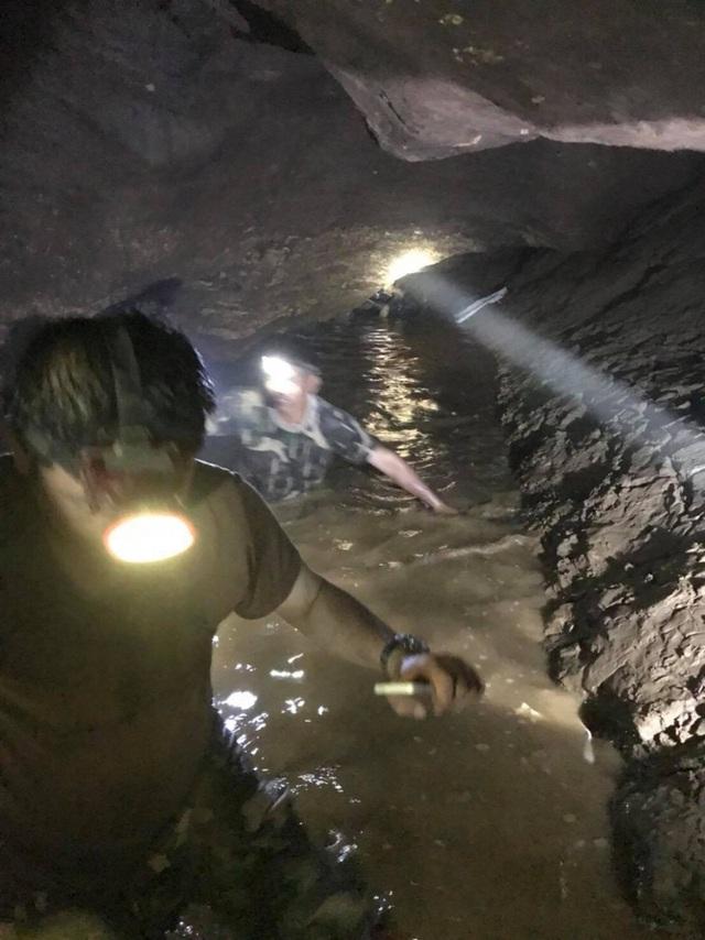 Lực lượng cứu hộ phải đội mũ có gắn đèn trên đầu khi lội nước trong hang. (Ảnh: The Nation)