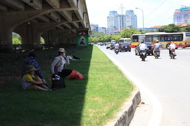 Nhiều người bắt xe khách từ Bến xe Mỹ Đình, mệt mỏi vì nắng nóng đã ngả lưng luôn trên thảm cỏ dưới chân đường trên cao vành đai 3, đoạn đối diện Bến xe Mỹ Đình.