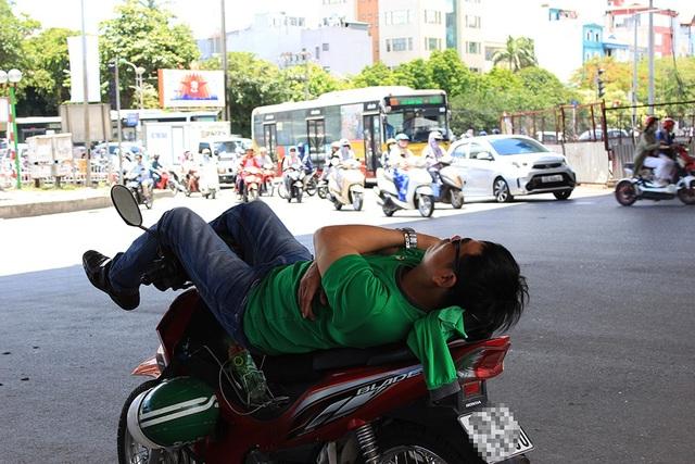 Một tài xế xe ôm ngả lưng dưới gầm cầu vượt đường Láng - Bưởi.