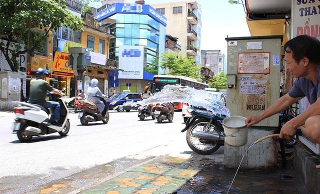 Trên phố Khâm Thiên, người đàn ông này liên tục đổ những xô nước ra trước cửa để giảm bớt hơi nóng hắt lên từ mặt đường nhựa.