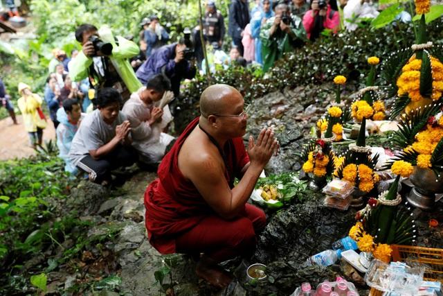 Nhà sư Thái Lan cầu nguyện bên ngoài hang Tham Luang Non (Ảnh: Reuters)