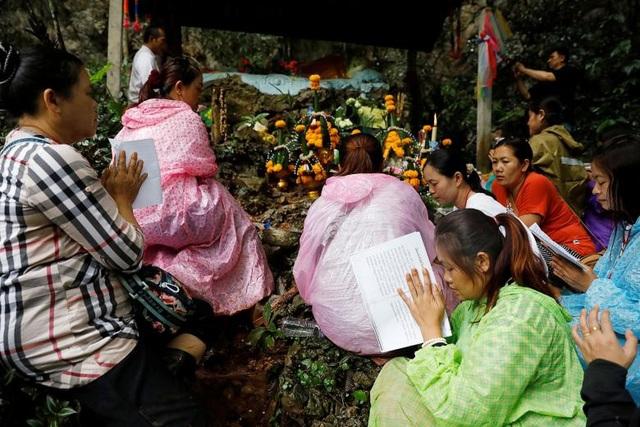 Gia đình của các thành viên đội bóng cầu nguyện bên ngoài hang (Ảnh: Reuters)