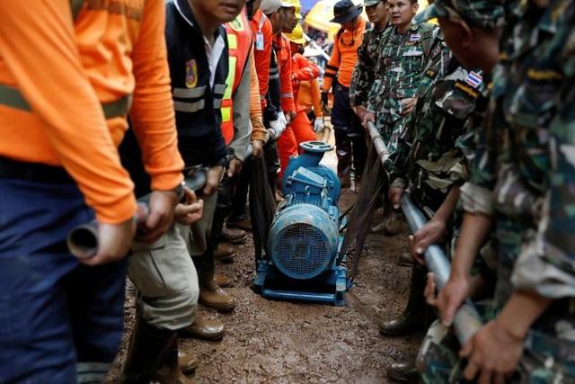 Các binh sĩ và lực lượng cứu hộ khiêng máy bay để hút nước ra khỏi hang (Ảnh: Reuters)