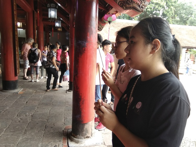 Học sinh Lê Vi, Trường THCS Phạm Hồng Thái đang cầu mong mình thi đỗ vào lớp 10 Trường THPT Phạm Hồng Thái. Cùng đi với Vi, có cả bố.