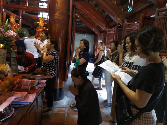Phụ huynh mang danh sách học sinh cả lớp đến đọc trước ban thờ.