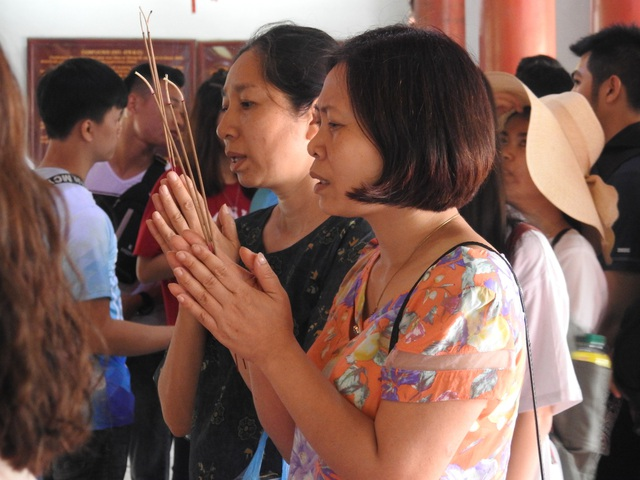 Phụ huynh em Ngọc Minh (áo hoa xanh) đang thắp hương cầu mong con em mình đỗ vào Trường THPT chuyên Nguyễn Huệ.