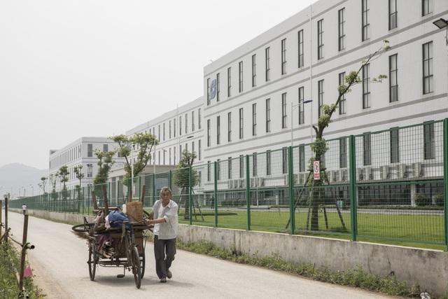 Một người đàn ông đang kéo một chiếc xe kéo phía trước nhà máy được điều hành bởi Tập đoàn Công nghệ Quang học Sunny. (Nguồn: Qilai Shen/Bloomberg)