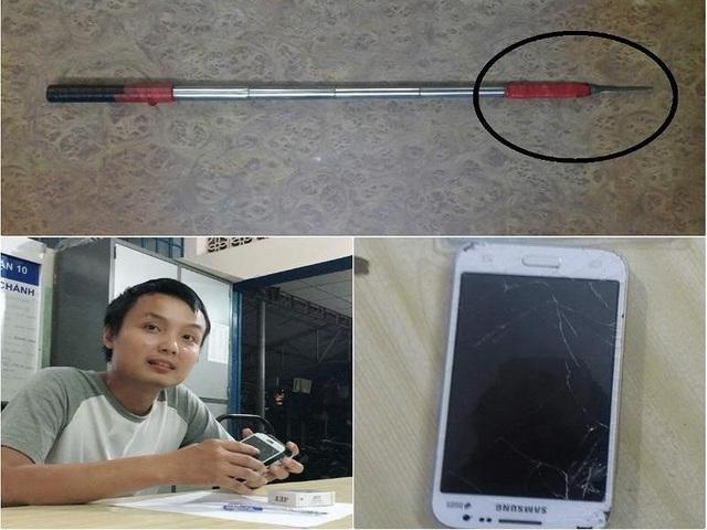 Anh Phạm Đình Thuận nâng niu chiếc điện thoại đã vỡ nát. Ảnh: NGUYỄN TRÀ.