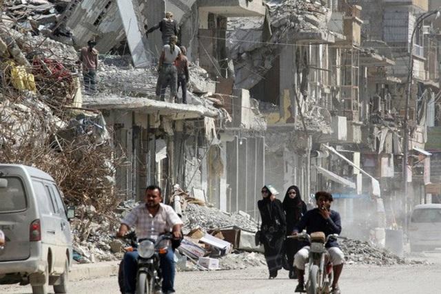 Những người phụ nữ đi qua đống đổ nát của những tòa nhà bị phá hủy ở Raqqa, Syria. Ảnh: Reuters