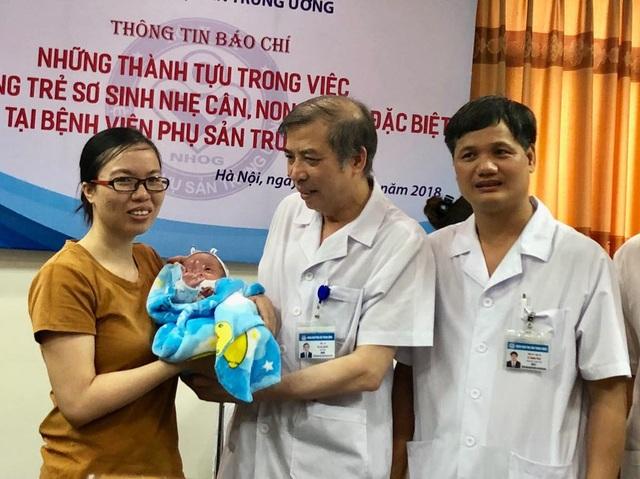 PGS.TS Vũ Bá Quyết, TS Lê Minh Trác trao em bé cho mẹ cháu. Ảnh: H.Hải