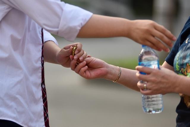 Một phụ huynh không quên chuẩn bị nước và đồng hồ cho con trước khi vào phòng thi.