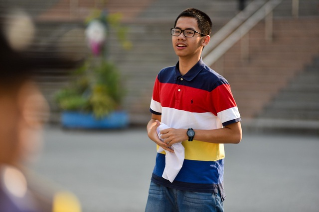 Một học sinh cầm vội chiếc áo trắng khi phụ huynh vừa mang tới.