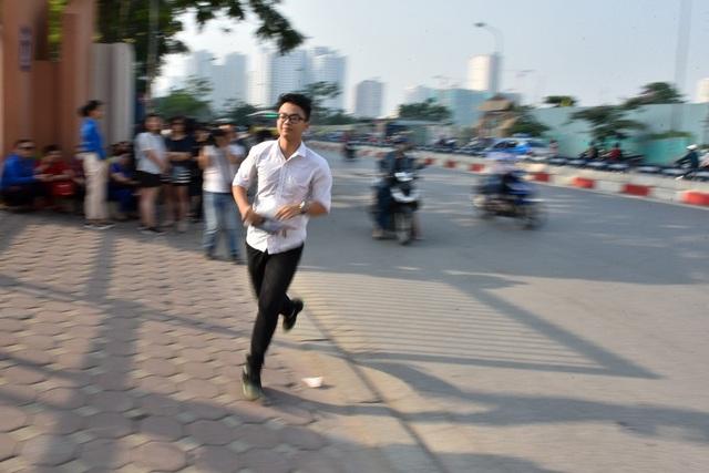 Sát giờ thi, một số thí sinh vội vã chạy tới cho kịp vào phòng thi trước giờ phát đề. (Ảnh: Toàn Vũ)