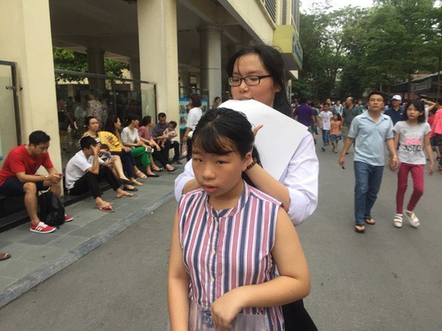Dù đã sát giờ vào phòng thi nhưng một tình nguyện viên là học sinh của trường vẫn buộc tóc cho một thí sinh trước khi bước vào kỳ thi quan trọng.