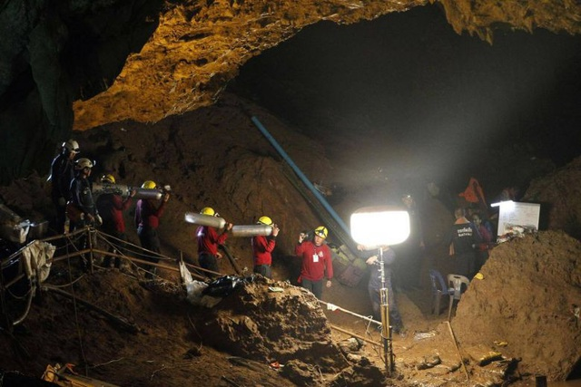 Đội cứu hộ vận chuyển các bình dưỡng khí vào bên trong hang khi các thợ lặn tiếp cận vào sâu bên trong. (Ảnh: EPA)