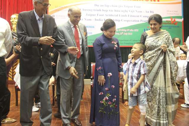 Bà Nguyễn Thị Hiền cùng Đại sứ Harish trò chuyện cùng một em nhỏ được lắp hai chân giả thuộc dự án hỗ trợ của Ấn Độ (Ảnh: Thành Đạt)