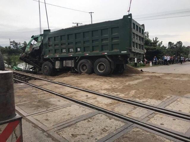 Chiếc xe hổ vồ chở cát bị tàu khách đâm hất văng khỏi đường sắt.