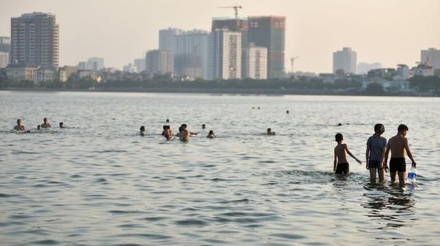 Chiều 11/9, hai ngày sau khi Hồ Tây xảy ra hiện tượng cá chết đồng loạt, nhiều người dân Hà Nội vẫn vô tư xuống hồ tắm giải nhiệt.