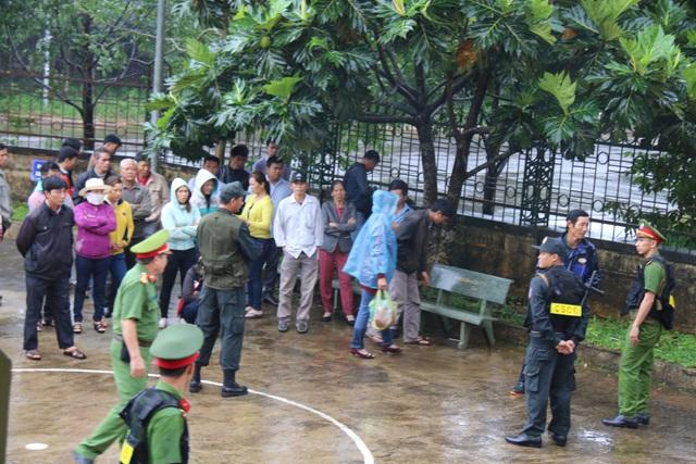 Người dân đội mưa đứng ngoài sân theo dõi phiên tòa vì không được vào trong