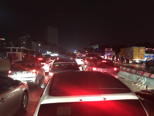 Dòng phương tiện bị ùn ứ kéo dài trên đường Phạm Văn Đồng hướng cầu Thăng Long lúc 19h30 tối nay, do đường bị ngập đoạn giao ngã tư Cổ Nhuế - Trần Cung.