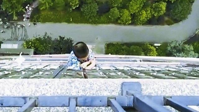 Bé trai trượt chân ngã và treo lơ lửng bên ngoài ban công tầng 19 hơn nửa giờ. (Ảnh: dzrbs.com)
