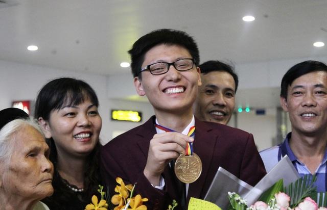Em Nguyễn Quang Bin, học sinh lớp 12, Trường Trung học phổ thông chuyên Khoa học Tự nhiên, Đại học Quốc gia Hà Nội đoạt Huy chương Vàng trong vòng tay chào đón của gia đình.