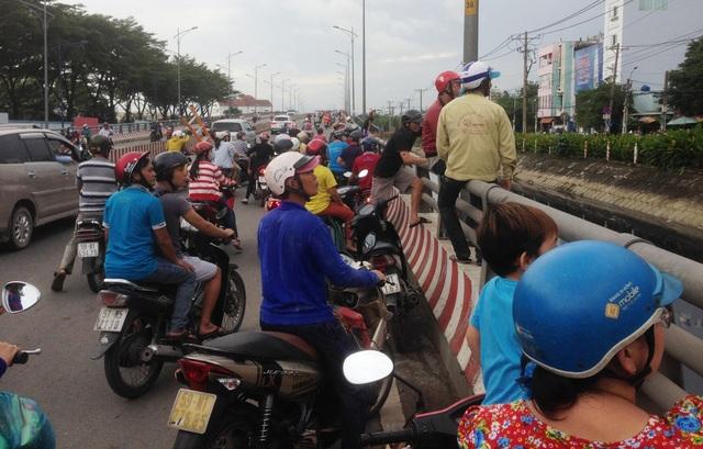 Người hiếu kỳ đứng trên cầu vượt Tân Tạo theo dõi vụ việc đã gây ảnh hưởng đến giao thông qua khu vực.