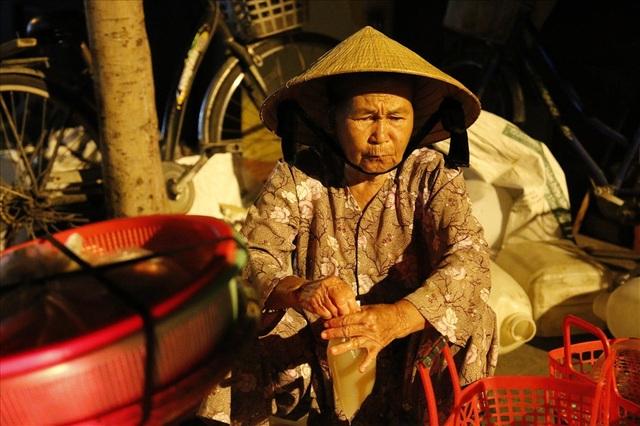 Bà Hồ Thị Năm (SN 1943) đang cho nước hến vào túi ni lông.