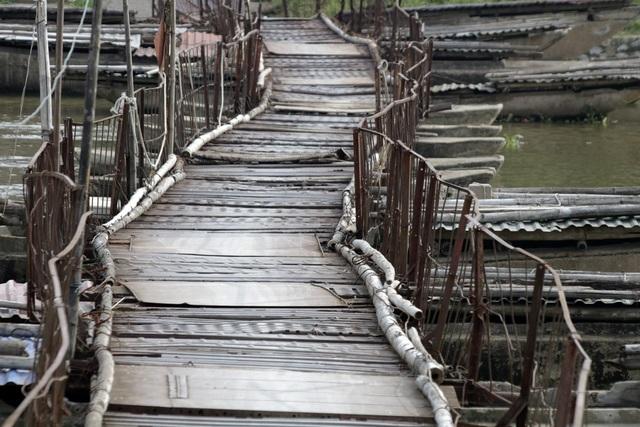 Cây cầu phao thô sơ được chằng kéo từ các sợi thép kêu lọc xọc dưới mỗi đợt người qua.