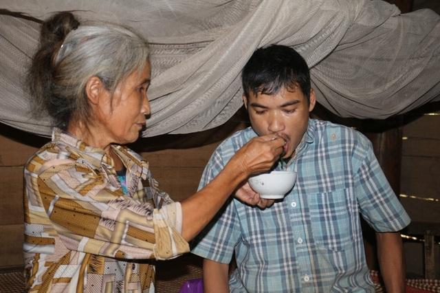 Bà Hương đang bón cơm cho đứa con trai năm nay gần 40 tuổi