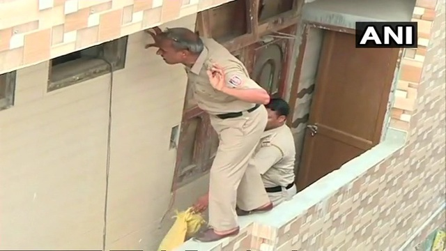 Cảnh sát có mặt tại hiện trường ngôi nhà nơi phát hiện 11 người chết trong tư thế treo cổ. (Ảnh: ANI)