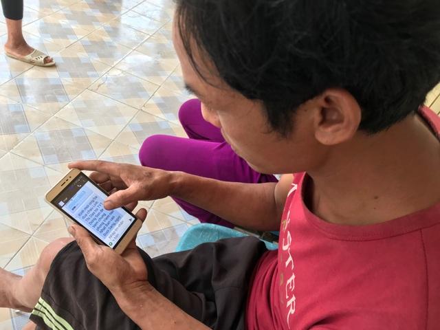 Một ông bố cẩn thận đọc lại tin nhắn nhắc tiêm chủng được gửi đến điện thoại di động của anh.