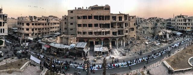 """Bức ảnh hàng dài người Syria ngồi ăn tối khi tháng ăn chay Ramadan kết thúc tại thành phố Douma (Syria) trong bối cảnh xung quanh bị tàn phá nặng nề bởi chiến tranh. Bức ảnh được Mohammed Badra (Syria) chụp bằng iPhone 7 đã giành giải nhất trong hạng mục ảnh """"Tin tức/Sự kiện"""""""