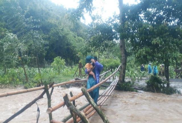 Các lực lượng của xã Chiêu Lưu đã kịp thời bắc cầu tạm qua khe ứng cứu được 4 người già và 1 cháu nhỏ ra khỏi vùng bị cô lập an toàn (Ảnh: Kỳ Sơn)