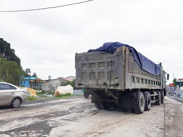Xe quá tải cày trên đường khiến mặt đường đã hư hỏng lại càng hư nát thêm.