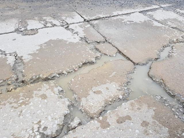 Từng khối bê tông mặt đường đổ dày khoảng 20cm, giờ đây bị băm nát bét khắp nơi.