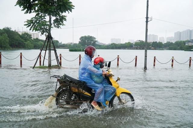 Nước dâng cao khiến người dân không thể phân biệt được giữa mặt đường và mặt hồ Văn Quán nếu như không có hàng cọc bên đường.