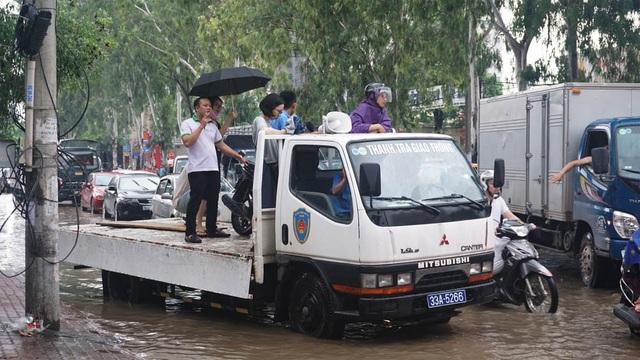 Xe của lực lượng thanh tra giao thông ngoài làm nhiệm vụ chuyên môn còn cho người dân đi nhờ qua chỗ ngập sâu.