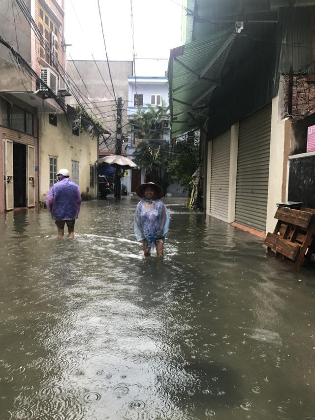 Giữa cơn mưa lớn, bà tổ trưởng tổ dân phố 11 lội nước thị sát nỗi khổ của người dân. Một bác Đại tá về hưu đi đo và đánh dấu mực nước ngập để chờ sẵn sàng cho việc nâng cốt đường như lãnh đạo UBND quận đã hứa với người dân.
