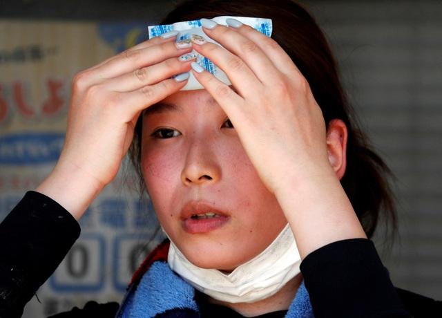 Một phụ nữ dùng miếng làm mát dán lên trán để hạ nhiệt cơ thể tại Okayama (Ảnh: Reuters)