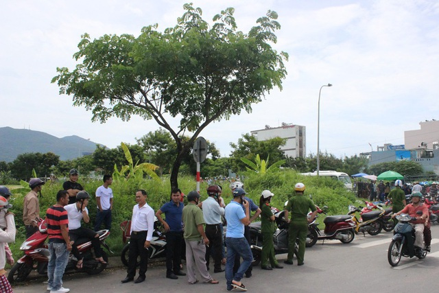 Người dân dõi theo vụ việc từ bên ngoài khu vực hiện trường đã được phong toả