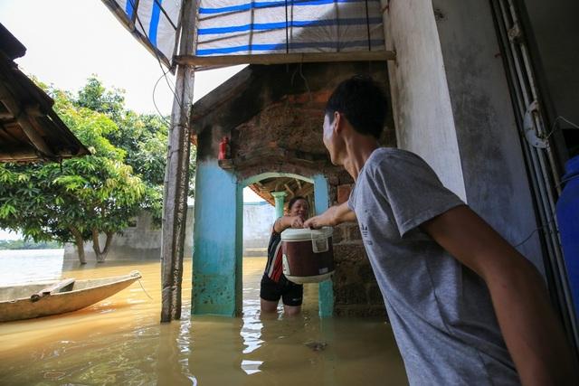 Gia đình anh Nguyễn Văn Mạnh đang chuẩn bị bữa cơm trưa trong khi nước vẫn ngập nửa nhà.