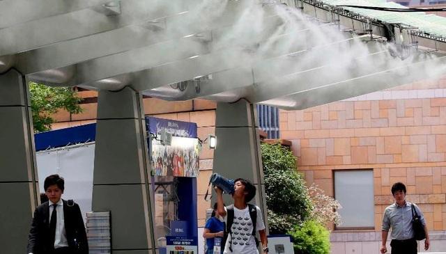Chính quyền Nhật Bản đã sử dụng nhiều cách để hạn chế tác động của nắng nóng tới cuộc sống của người dân, từ sơn đường để ngăn ánh sáng mặt trời cho tới lắp đặt các trạm phun sương công cộng. (Ảnh: AP)