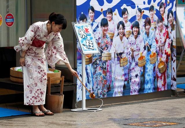Đợt nắng nóng kỷ lục diễn ra không lâu sau trận lũ lụt tàn phá khu vực miền tây và miền trung Nhật Bản khiến hơn 220 người thiệt mạng. Trong ảnh: Nước được vẩy trên đường để hạn chế hơi nóng bốc lên (Ảnh: Reuters)