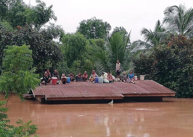 Người dân đứng trên mái nhà sau khi nước nhấn chìm nhiều làng mạc sau sự cố vỡ đập (Ảnh: ABC Laos)