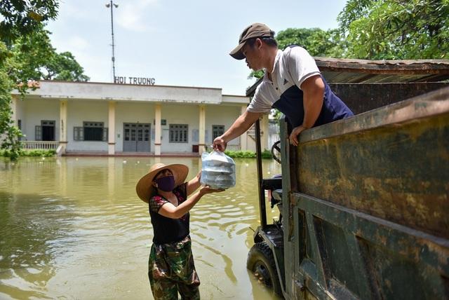 Trưa đến, cán bộ y tết xã và lực lượng dân quân tự vệ tổ chức chốt trực được tiếp viện cơm hộp từ ngoài vùng nước ngập.