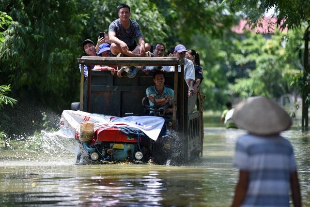 Chính quyền xã Nam Phương Tiến đã bố trí xe công nông gầm cao để đưa đón người dân đi lại trong những ngày nước ngập.